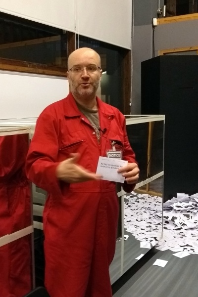 Artist Pete Ashton standing in BOM next to a Black Box with print-outs of paper on the floor