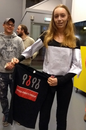 Female student Georgia wearing fancy dress and holding an ORG t-shirt